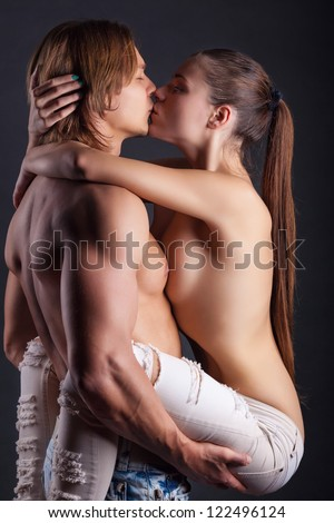 Young couple makes love on dark background - stock photo
