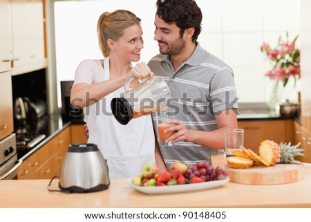 Young couple making fresh fruits juice in their kitchen - stock photo