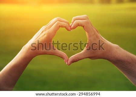 Young couple making heart. Female and male hands in the form of heart isolated on beautiful sunset. - stock photo