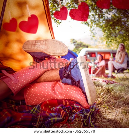 Young couple making out in tent against hearts hanging on a line