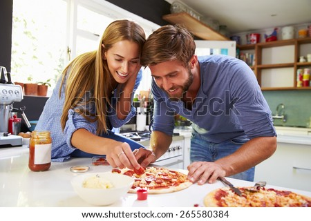 Young Couple Making Pizza In Kitchen Together - stock photo