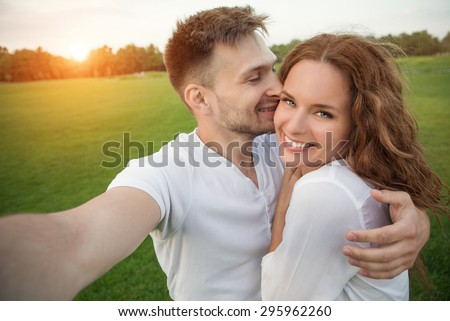 Young couple making selfies in the nature in beautiful sunset. Man kissing his girl-friend, girl with long red hair is smiling. - stock photo