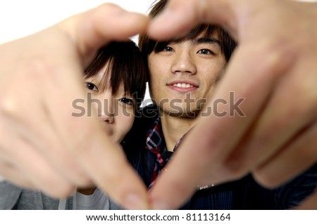 Young couple making the shape of a heart with hands and looking through it - stock photo