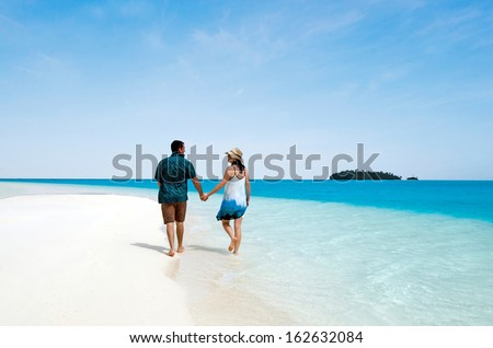 Young couple, male and female visit  Aitutaki Lagoon, Cook Islands.  Concept photo of couples travel , vacation, tourism , holidays, honeymoon, love,relationship. - stock photo