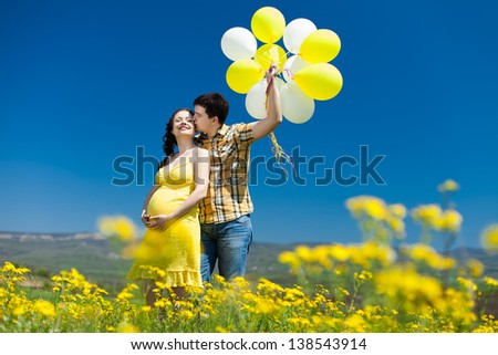 young couple man and his pregnant wife in a field with balloons - stock photo