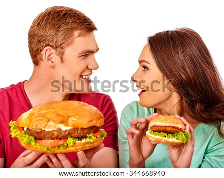 Young couple man and woman eating hamburgers big and small   . Fastfood concept.  Isolated. - stock photo