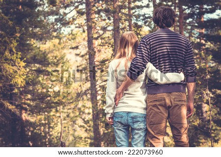 Young Couple Man and Woman Hugging in Love Romantic Outdoor with forest nature on background Fashion trendy style - stock photo