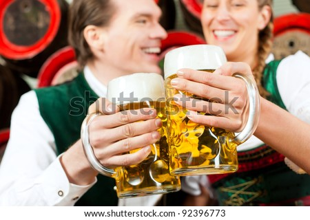Young couple, man and woman, in traditional Bavarian Tracht drinking beer in a brewery in front of beer barrels - stock photo