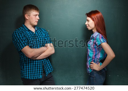 Young couple, man and woman make a claim to each other looking in eyes each other. Collision of interests in relationships. Red-haired woman and blonde man in check shirts. - stock photo