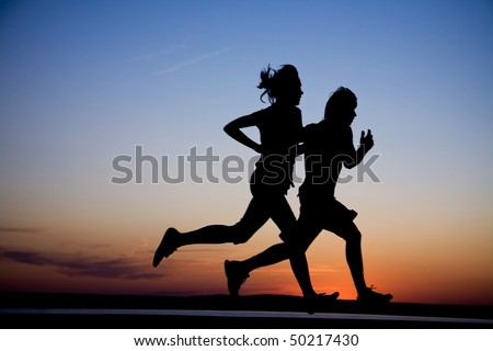 Young couple: man and  woman run together on a sunset on lake coast.  Silhouette.