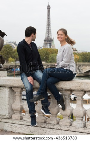 young couple man and woman sitting on the bridge on river Seine, Paris, France, in front of Eiffel Tower - stock photo