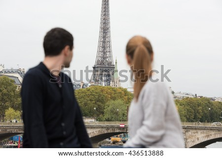 young couple man and woman sitting on the bridge on river Seine, Paris, France, in front of Eiffel Tower