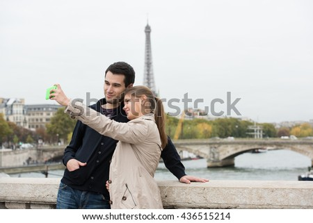young couple man and woman sitting on the bridge on river Seine, Paris, France, in front of Eiffel Tower, making selfie with smart phone - stock photo