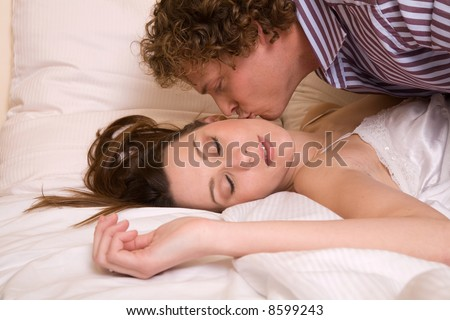 Young couple; man bending over his girlfriend kissing her goodbye - stock photo