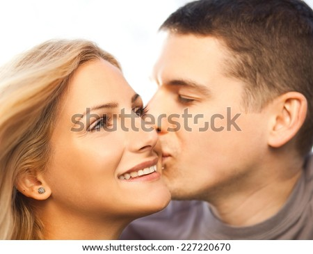 Young couple - man kissing woman on the cheek