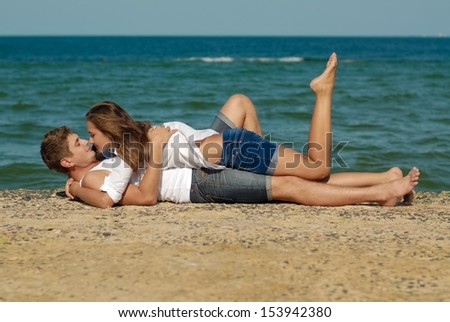 Young couple man & woman loving each other on sea or ocean beach in summer outdoors - stock photo