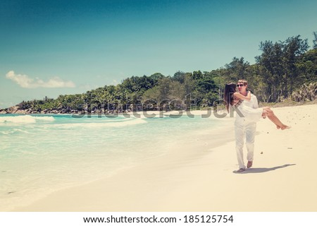 Young couple married on sandy beautiful tropical beach Seychelles La Digue - stock photo