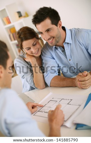 Young couple meeting architect for future house - stock photo