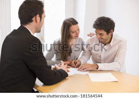 Young Couple meeting real-estate agent to buy property - stock photo