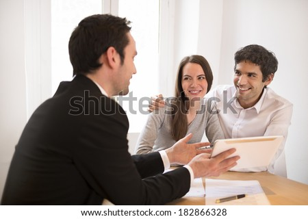 Young Couple meeting real-estate agent to buy property, presentation on the tablet pc - stock photo