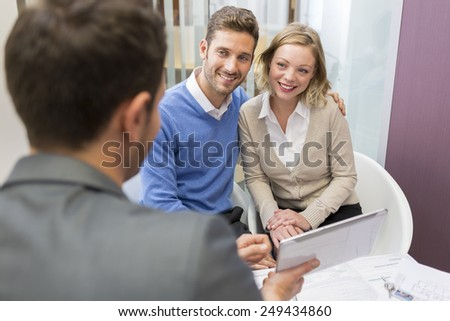 Young couple meeting real-estate showing a investment project on a tablet pc - stock photo