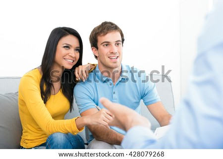 Young couple meeting with  consultant (or counselor, financial adviser, real estate agent etc.) - stock photo