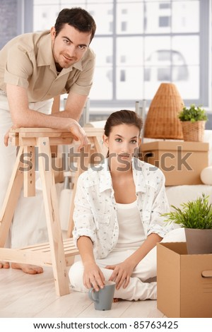 Young couple moving home, sitting on floor, boxes around, smiling, drinking tea.? - stock photo