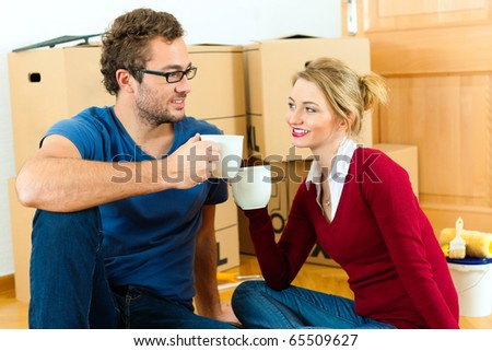 Young couple moving in a home or apartment, they are sitting on the wood floor drinking coffee having a break from renovation