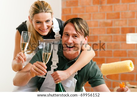Young couple moving in new flat doing renovation and painting, celebrating their new home with sparkling wine - stock photo