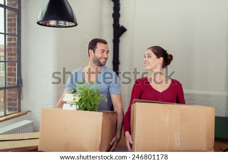 Young couple moving into a new house standing side by side holding packing cartons looking at each other with a smile - stock photo