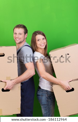 Young couple moving into their new home standing back to back in front of a recently redecorated green wall holding brown cardboard boxes and smiling at the camera - stock photo