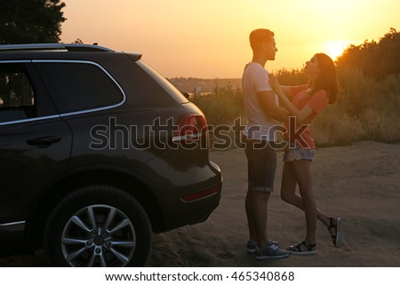 Young couple near car on sunset background