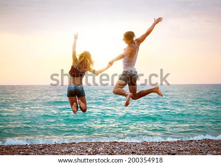 Young couple near the sea at sunset jumping - stock photo