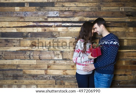 Young couple near wooden wall celebrating Christmas with present. Love and relationship concept.