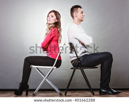 Young couple not talking to each other and sitting back to back after argument quarrel. Disagreement in relationship. Angry man and offended woman get mad. - stock photo