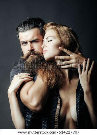 young couple of bearded handsome man and sexy woman or girl with pretty face has long blonde hair embracing on grey background