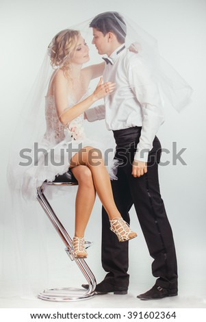 young couple of bride in stylish wedding dress and groom covered with veil