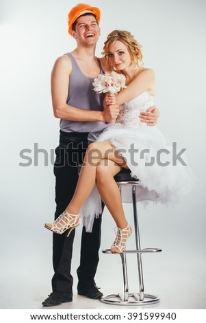 young couple of bride with bunch of flowers in stylish wedding dress and groom in helmet and sleeveless vest