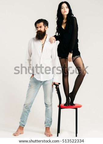 young couple of handsome bearded man in shirt and jeans with pretty sexy woman or girl in black stockings with long hair stands on chair in studio isolated on white background