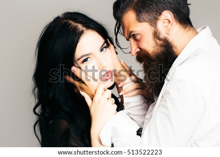 young couple of handsome bearded man in white shirt with pretty sexy woman or girl with long black hair embracing in studio on grey background