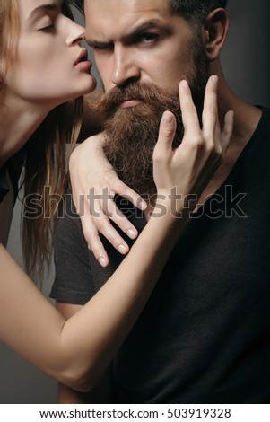 young couple of handsome bearded man with long beard and pretty sexy woman or girl with cute face and red hair embraces in studio on black background