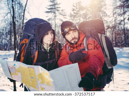 Young couple of hikers pointing at direction