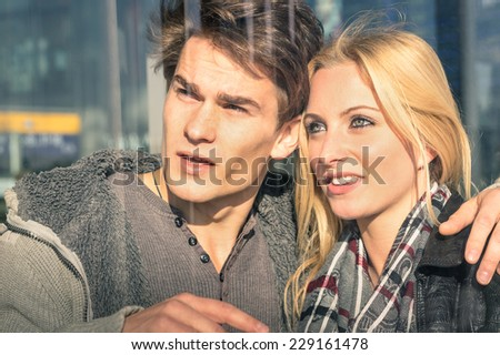 Young couple of lovers behind glass reflections - Handsome man and beautiful woman watching something around - Beginning of a love story on a vintage filtered look - stock photo
