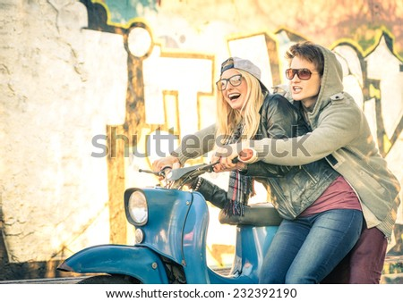 Young couple of lovers haviing fun on a vintage scooter moped - Handsome man in playful attitude with his beautiful girlfriend - Beginning of a love story on a warm sunny winter day - stock photo