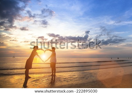 Young couple of lovers on a tropical beach holding hands forming a heart. - stock photo