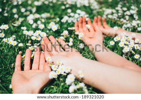 Young couple of lovers relaxing lying on spring flowers. Man and woman enjoying love relationship and leisure vacation together. - stock photo