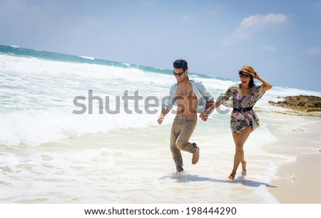 Young couple of lovers running in a white tropical beach - stock photo