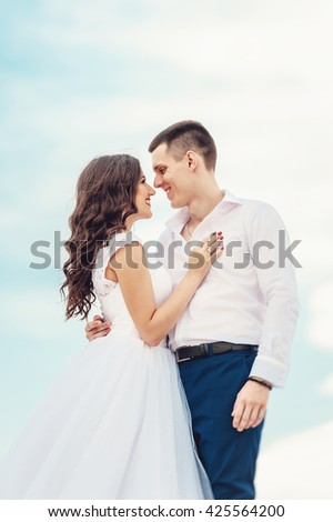 Young couple of newlyweds kissing and smiling brightly. Stylish man and beautiful woman on their wedding day against blue sky. Happy wife and husband kissing and embracing. - stock photo
