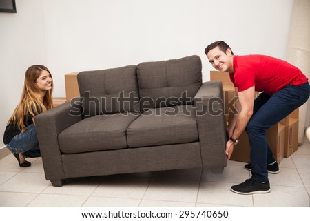 Young couple of newlyweds trying to move a couch to their new apartment - stock photo