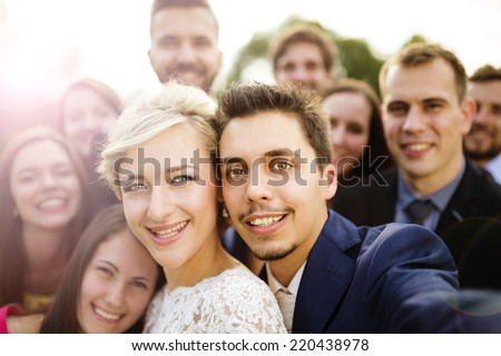 Young couple of newlyweds with group of their firends taking selfie - stock photo